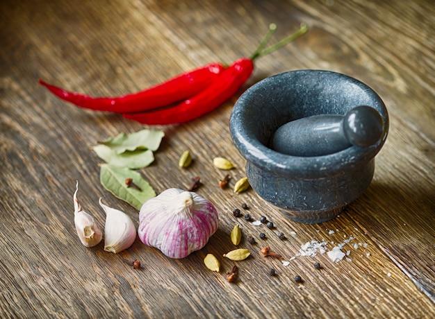 Especiarias, alho e pimenta vermelha em uma mesa de madeira
