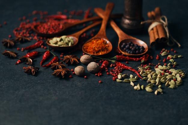 Especiarias aromáticas em colheres de madeira na mesa de pedra escura