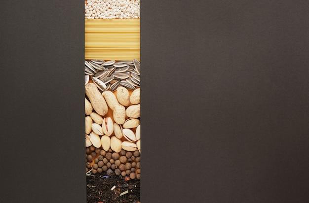 Especiarias, chá, cereais, nozes, sementes e textura de massa, papel preto para seu texto, cópia do espaço simulado, vista superior do conceito de mercearia