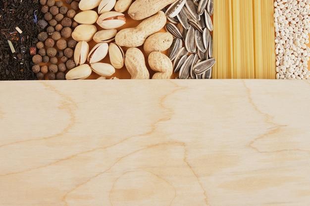 Especiarias, chá, cereais, nozes, sementes e textura de massa, placa de madeira para o seu texto, cópia do espaço simulado, vista superior do conceito de mercearia