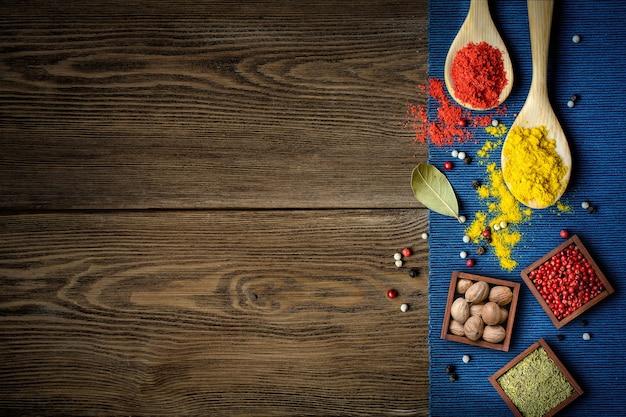 Especiarias coloridas em pó em colheres e em uma caixa de madeira no fundo da mesa de madeira escura com borda de pano azul, vista superior com espaço de cópia