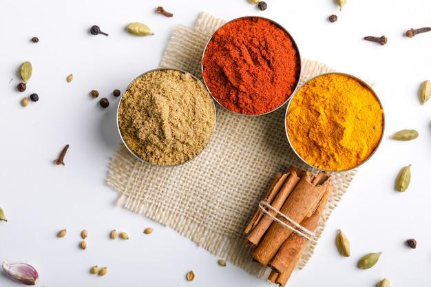 Especiarias coloridas indianas vermelho pimenta em pó, pó de cúrcuma, coentro em pó na mesa branca