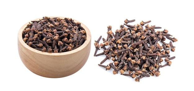 Especiarias de cravo em uma tigela de madeira no fundo branco