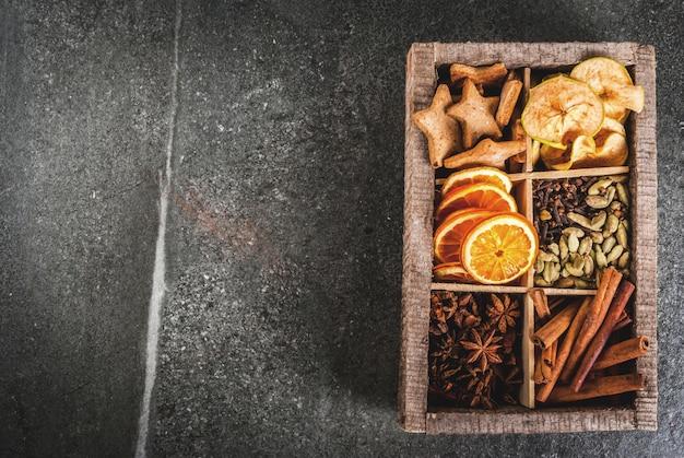 Especiarias de natal para assar, coquetéis, vinho quente, com biscoitos de gengibre (estrelas) - maçã seca, laranja, cardamomo, cravo, canela, anis. caixa de madeira velha, mesa de pedra preta. copie o espaço vista superior