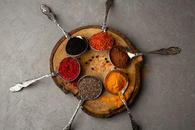 Especiarias diferentes coloridas dentro de colheres de prata na mesa de madeira marrom na mesa cinza
