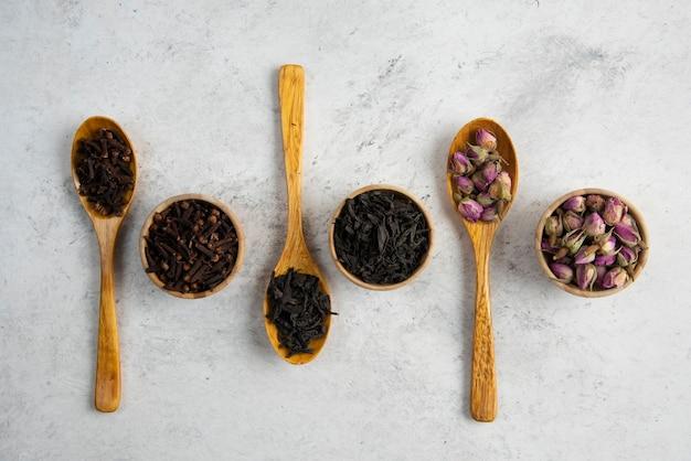 Especiarias diferentes em tigelas e colheres de madeira.