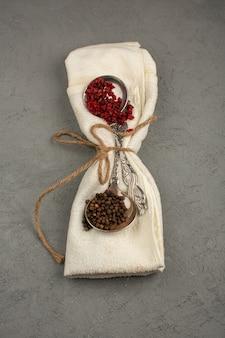 Especiarias diferentes vermelho e marrom picante quente em uma toalha de creme em um piso cinza