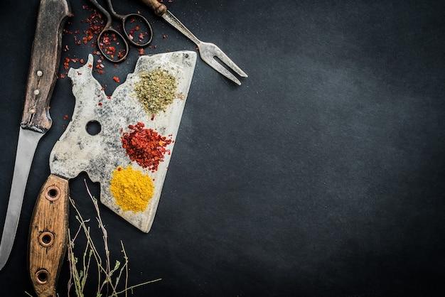 Especiarias e ervas com velho machado de cozinha