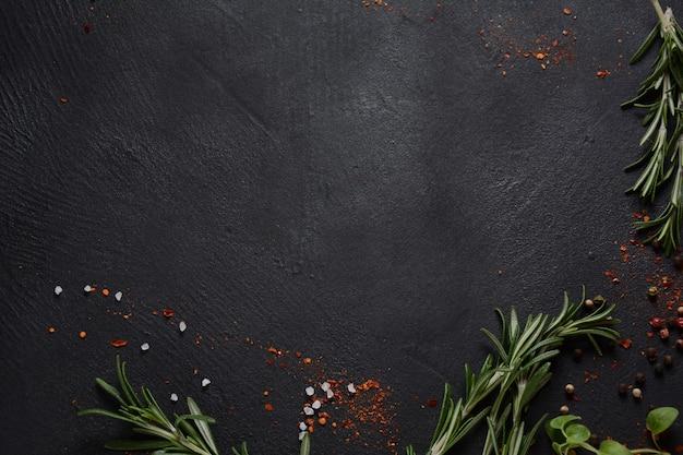 Especiarias e ervas em fundo de pedra escura