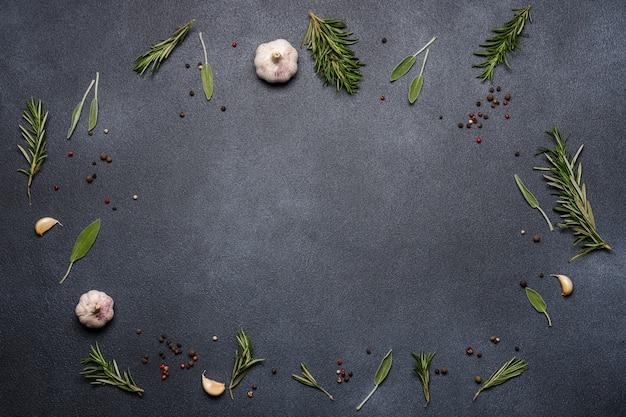 Especiarias e ervas em fundo preto. alecrim, sálvia, pimenta, alho.