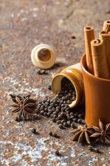 Especiarias e ervas. ingredientes alimentares e gastronômicos. paus de canela, estrelas de anis, pimenta preta em plano de fundo texturizado
