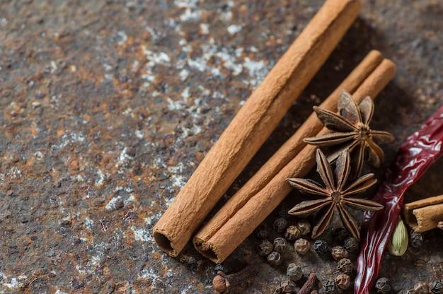 Especiarias e ervas. ingredientes alimentares e gastronômicos. paus de canela, estrelas de anis, pimenta preta, pimentão, cardamomo e cravo no plano de fundo texturizado