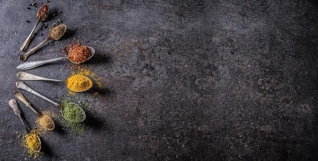 Especiarias e ervas para cozinhar em fundo escuro - topo da vista.