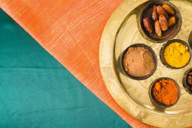 Especiarias e frutas secas na bandeja em têxteis