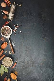 Especiarias e moedor de pimenta vintage em fundo preto de concreto