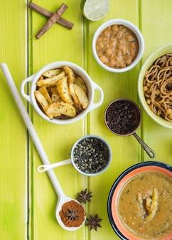 Especiarias e pratos aromáticos na mesa verde