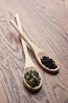 Especiarias em colheres de madeira na mesa de madeira