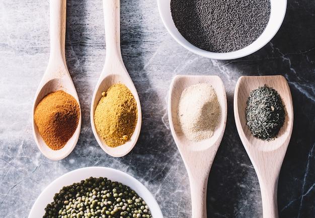 Especiarias em colheres, sementes de chia e feijão verde em taças.