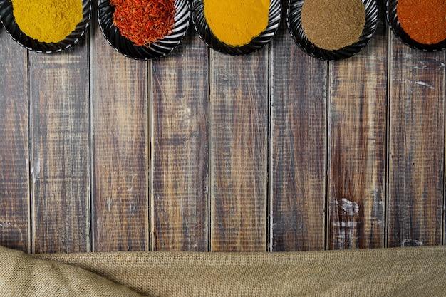 Especiarias em placas de cerâmica pretas sobre fundo de madeira. seleção de várias especiarias. seis pratos com especiarias coloridas diferentes perto de saco.