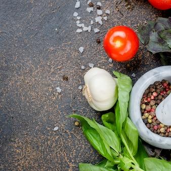 Especiarias em um almofariz de pedra, manjericão verde e tomate