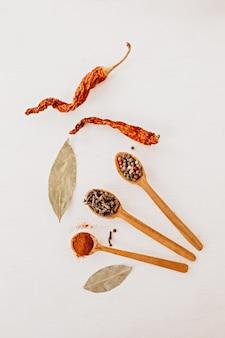 Especiarias em uma colher de pau. ervas, curry, açafrão, açafrão, canela, louro, pimentão para cozinhar em um fundo branco Foto Premium