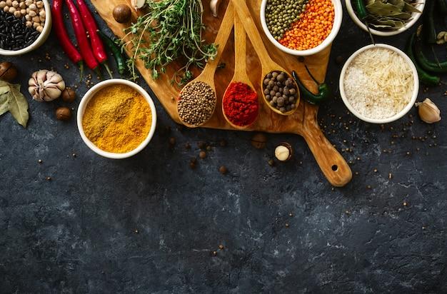Especiarias, ervas, arroz e vários feijões e temperos para cozinhar no backgraund escuro com vista superior copyspace