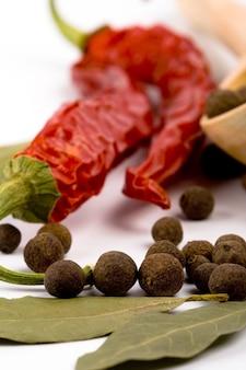 Especiarias: folhas de louro, pimenta, pimentão e colher de pau closeup