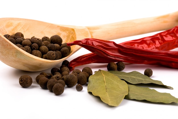 Especiarias: folhas de louro, pimenta, pimento no close up de madeira da colher no fundo branco.