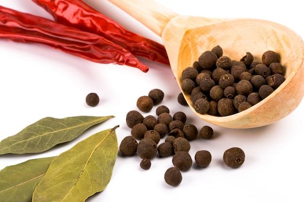 Especiarias: folhas de louro, pimentão, pimenta aromática na colher de pau closeup