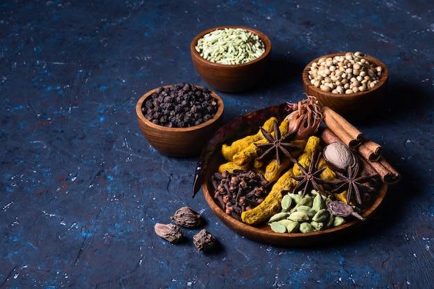 Especiarias indianas de aquecimento seco na placa para a refeição do inverno do outono na obscuridade - concreto azul.