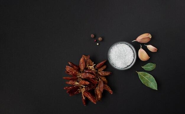 Especiarias isoladas em fundo preto, alho, sal, folhas de louro e variedade de especiarias de pimenta vermelha quente