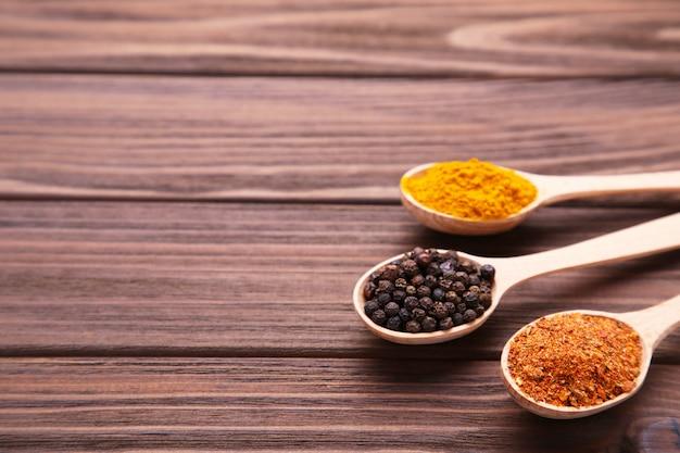 Especiarias misturam na colher em uma mesa de madeira marrom.