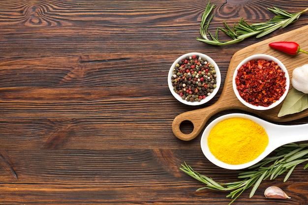 Especiarias na colher e tigelas na mesa de madeira