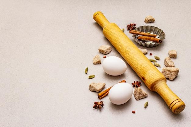 Especiarias, ovos, açúcar mascavo, assadeira de cupcake e um rolo. luz