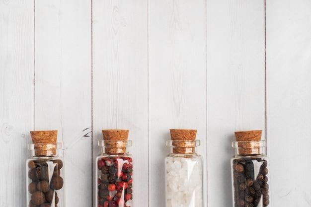 Especiarias, pimenta preta e vermelha e sal em frascos de vidro