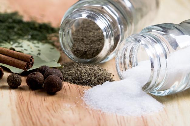Especiarias: pimenta, sal, louro, canela e ervas closeup em fundo de madeira