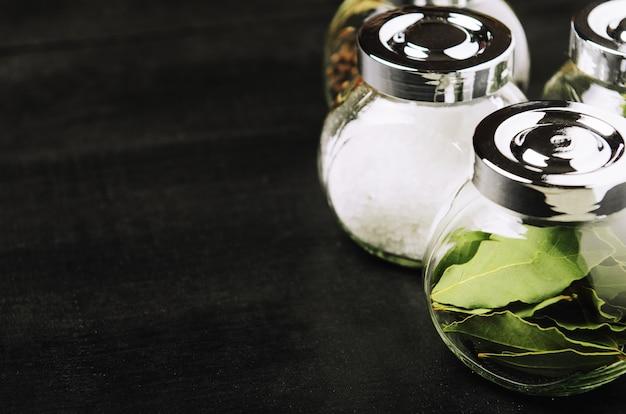 Especiarias populares em frascos pequenos no fundo preto.