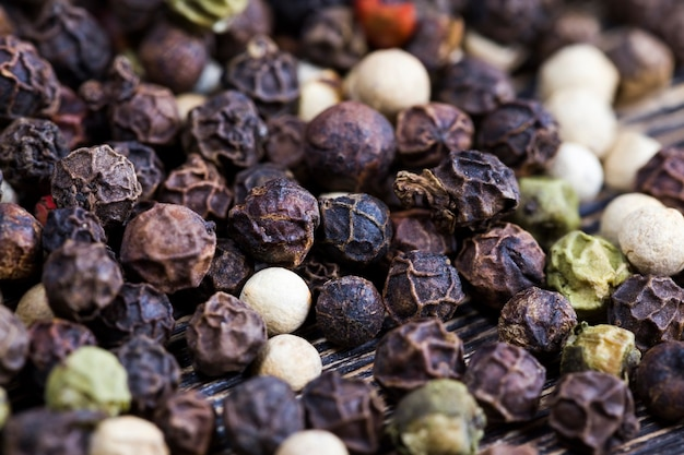 Especiarias secas pimenta de ervilhas pretas em uma velha mesa de madeira na cozinha