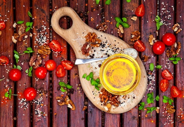Especiarias, tomate cereja, manjericão e óleo vegetal na mesa de madeira escura, vista superior