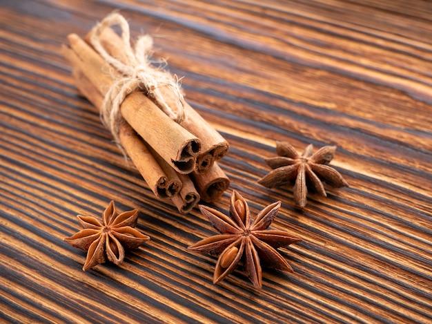 Especiarias tradicionais de natal - anis estrelado, paus de canela amarrados com corda em uma superfície de madeira escura e texturizada. nitidez selecionada.