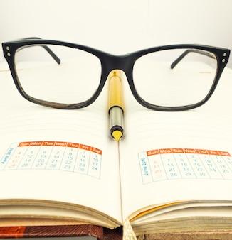 Especificações e caneta dourada no caderno ou no diário