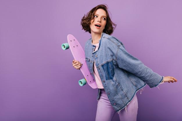 Espectacular jovem numa jaqueta grande dançando. retrato de uma menina encaracolada sonhadora com skate.