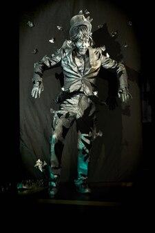 Espectacular show de pantomima realizado por um artista com expressão facial de surpresa, vestido em um terno pintado de cinza que lembra uma estátua. ator de mímica emocional em pé e gesticulando na parede de fundo preto