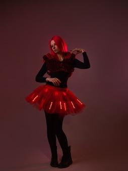 Espectáculo de luzes, fato com leds. bela jovem em um terno luminoso, tons de vermelho