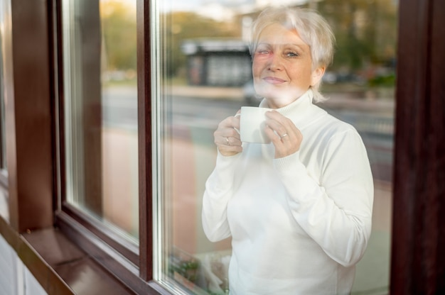 Espelhar o café bebendo fêmea sênior