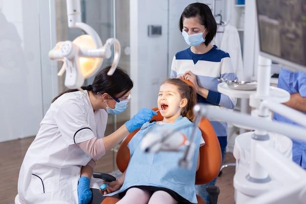Espelho angular usado pelo médico dentista na menina com a boca aberta no consultório odontológico. odontologista durante consulta de cárie infantil em consultório de estomatologia com tecnologia moderna.