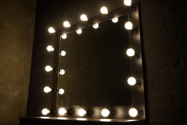 Espelho antigo com lâmpadas em fundo preto