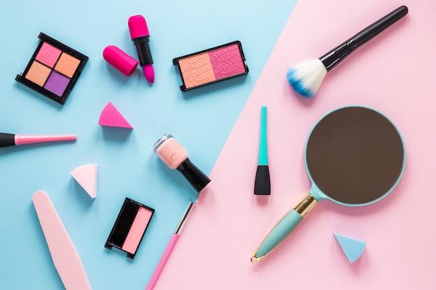 Espelho com diferentes cosméticos na mesa brilhante