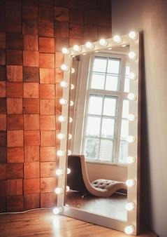 Espelho com lâmpadas contra uma parede de madeira