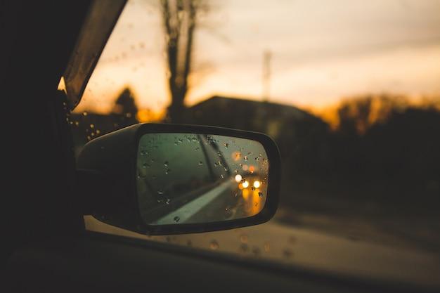 Espelho de carro com gotas no fundo por do sol. estrada em uma viagem